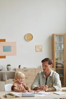 Pai fazendo lição de casa com seu filho pequeno na mesa ele explicando para ele o novo assunto na sala