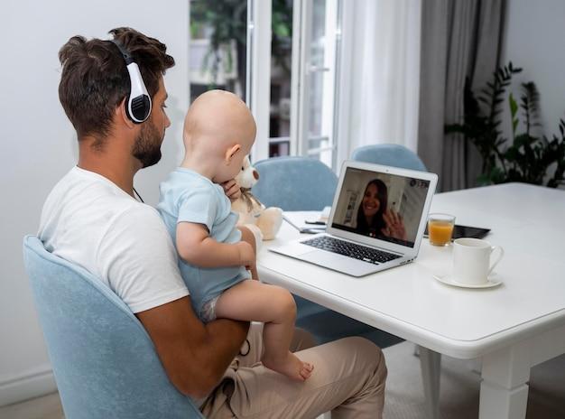 Pai fazendo videochamada para mãe com filho durante a quarentena