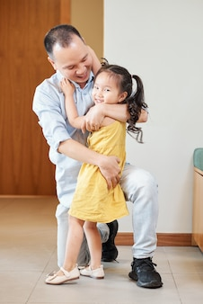 Pai feliz abraçando sua adorável filhinha sorridente