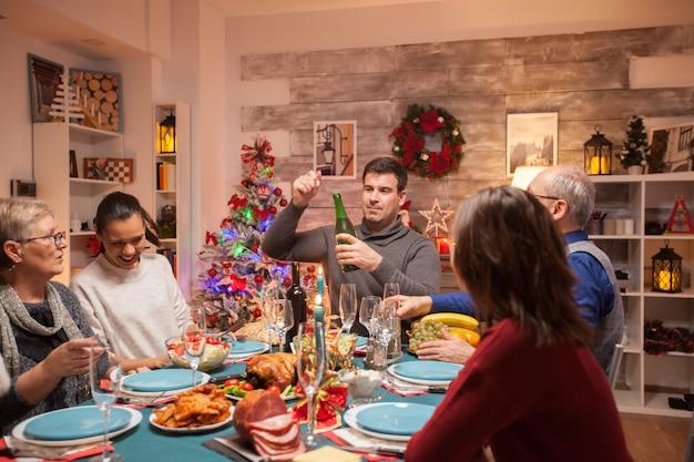 Pai feliz abrindo uma garrafa de vinho no jantar de natal em família. comida deliciosa.