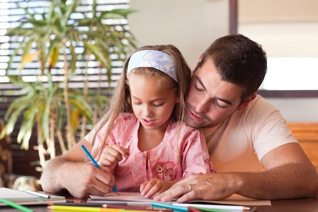Pai feliz ajudando sua filha a fazer a lição de casa
