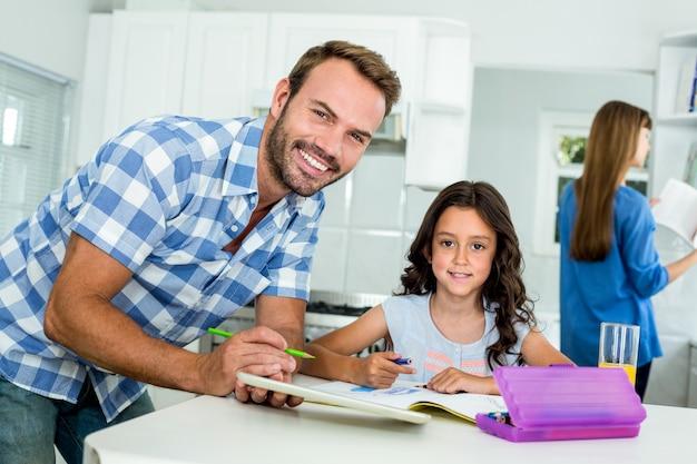 Pai feliz, auxiliando a garota na lição de casa em casa