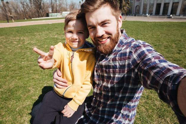 Pai feliz barbudo sentado ao ar livre com seu filho pequeno