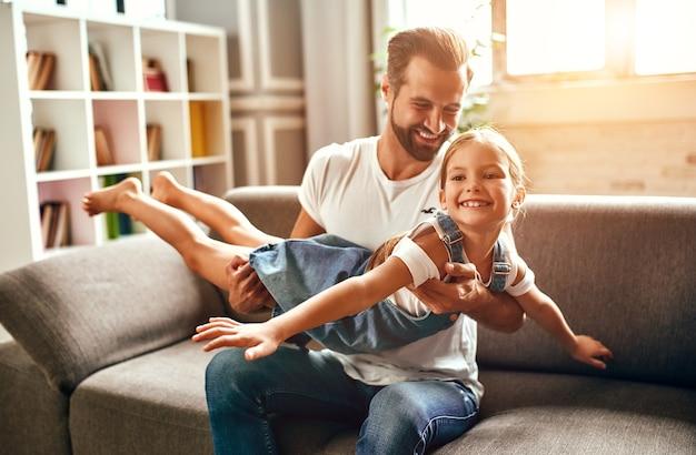 Pai feliz brincando, brincando com sua filha no sofá da sala de estar em casa. feliz dia dos pais.