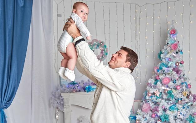 Pai feliz brincando com o filho perto da árvore de natal