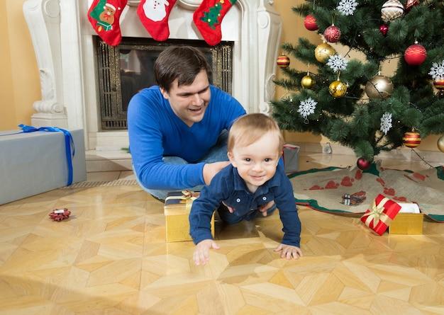 Pai feliz brincando com seu filho bebê no chão debaixo da árvore de natal