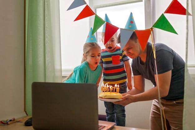 Pai feliz com dois irmãos comemorando aniversário via internet em tempo de quarentena, auto-isolamento