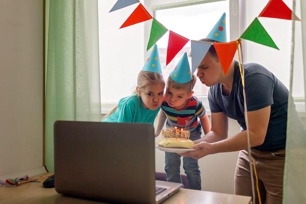 Pai feliz com dois irmãos comemorando aniversário via internet em tempo de quarentena