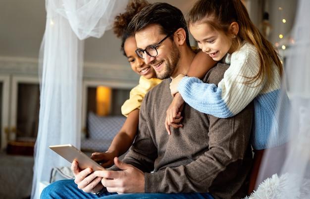 Pai feliz com filhas multiétnicas brincando com tablet digital em casa
