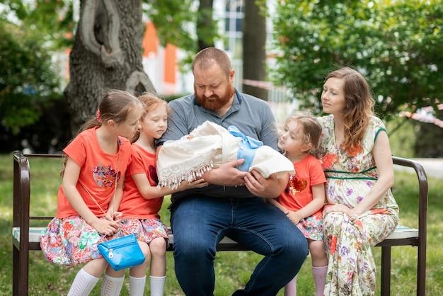 Pai feliz com muitos filhos segura o filho tão esperado nos braços grande família amigável