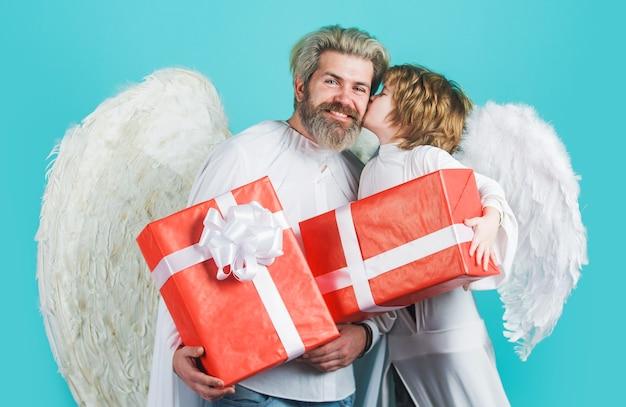 Pai feliz com o filho em fantasias de anjo com presentes.