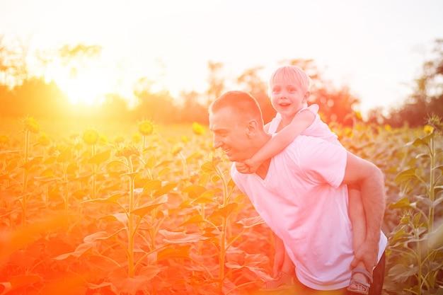 Pai feliz com o filho nas costas, andando em um campo verde de girassóis florescendo ao pôr do sol