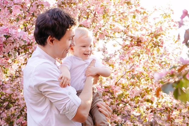 Pai feliz com seu filho no fundo de uma árvore florescendo no quintal da casa