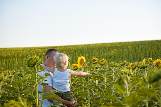 Pai feliz com seu filho pequeno nos braços em pé em um campo verde de girassóis contra um céu azul