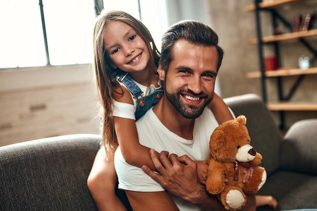 Pai feliz com sua filha fofa e ursinho de pelúcia abraço e divirta-se sentado no sofá da sala de estar em casa. feliz dia dos pais.