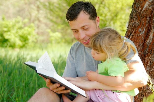 Pai feliz com um filho lendo um livro sobre a natureza da bíblia