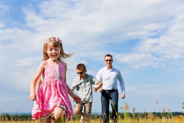 Pai feliz correndo com seus filhos na natureza
