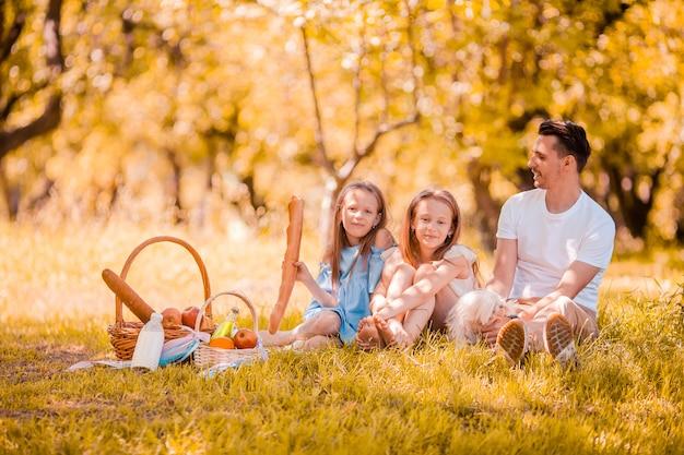 Pai feliz e filhas pequenas relaxar à beira do lago
