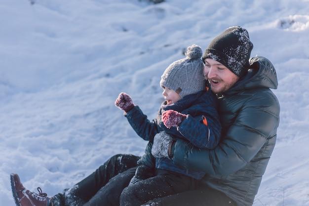 Pai feliz e filho brincando de trenó de neve