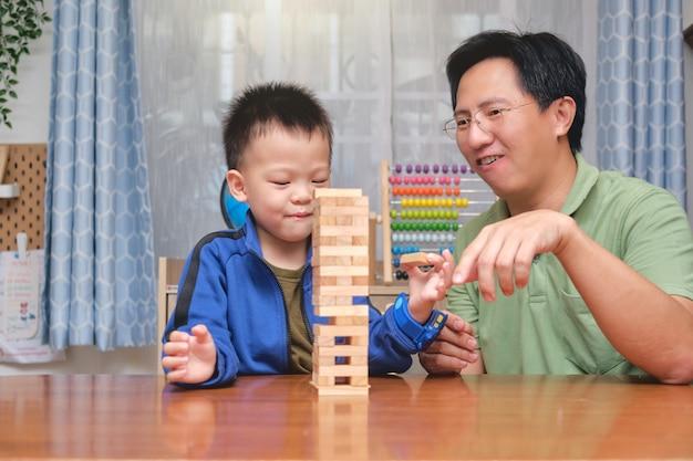 Pai feliz e filho de um menino asiático fofo animado com o jogo de blocos de madeira, pai e filho passando um tempo juntos