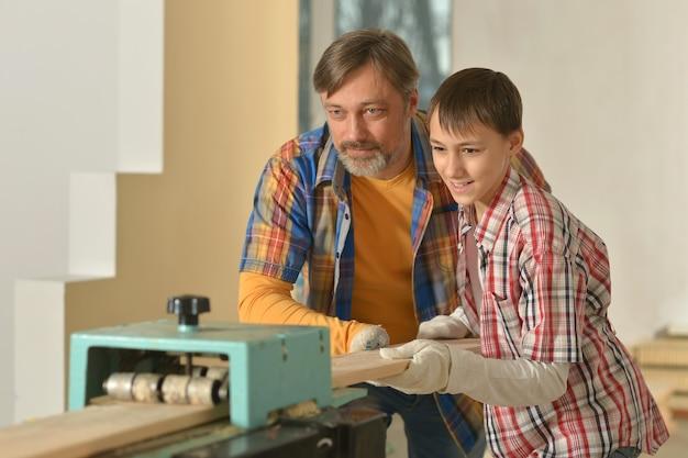 Pai feliz e filho fazendo reparos na sala