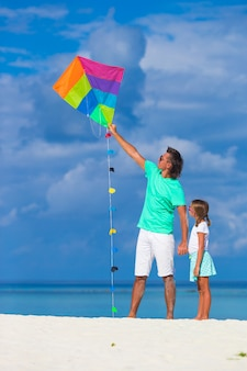 Pai feliz e menina empinando pipa juntos na praia tropical