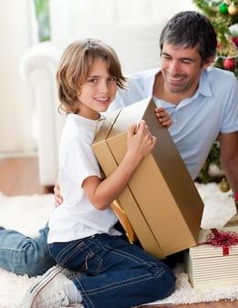 Pai feliz e seu filho abriram presentes de natal