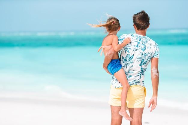 Pai feliz e sua adorável filha pequena na praia tropical se divertindo.