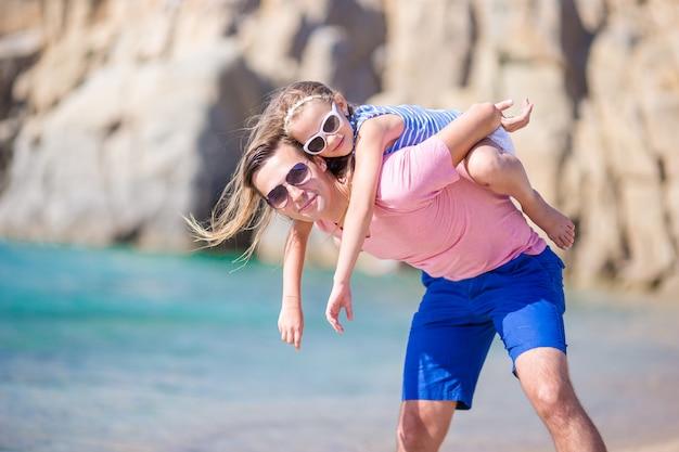 Pai feliz e sua adorável filha pequena na praia tropical se divertindo