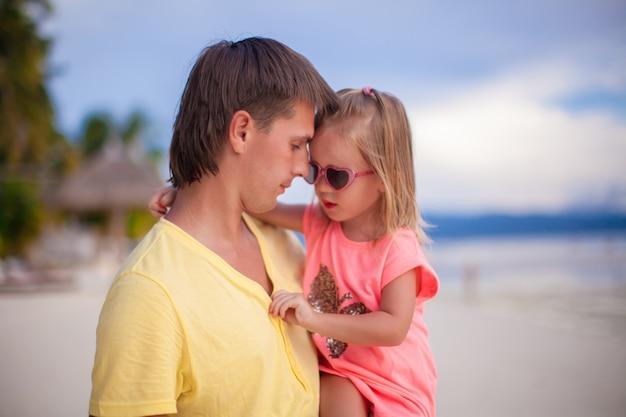 Pai feliz e sua filha pequena na praia de areia branca