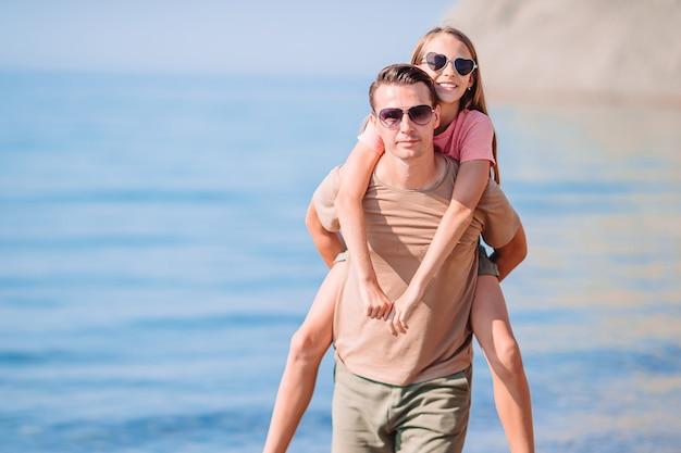 Pai feliz e uma menina na praia de areia branca se divertindo juntos