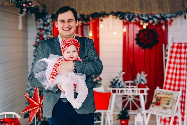 Pai feliz em roupas elegantes com sua filha junto na sala de férias decoradas com uma árvore de natal e uma coroa de flores