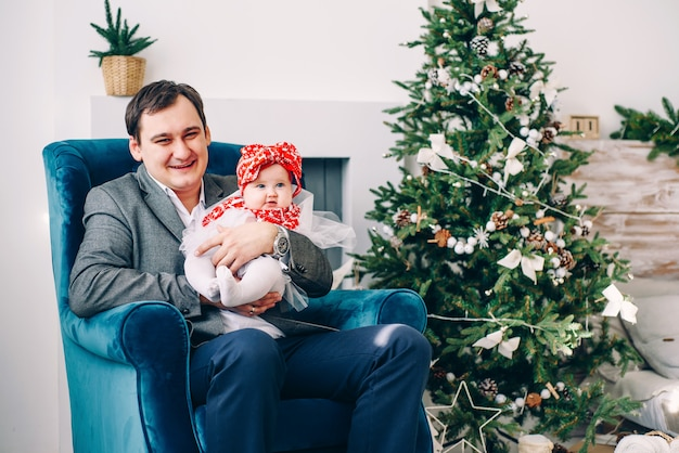 Pai feliz em roupas elegantes com sua filha pequena no vestido sentado na cadeira na sala de férias decoradas com uma elegante árvore de natal