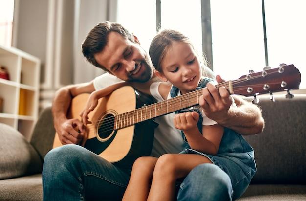 Pai feliz ensina sua linda filha a tocar violão enquanto está sentado no sofá da sala de estar em casa. feliz dia dos pais.