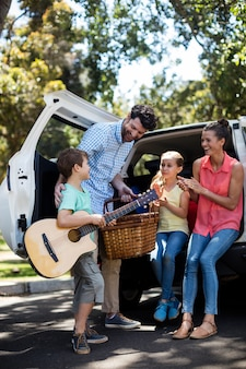 Pai feliz interagindo com seu filho perto de carro
