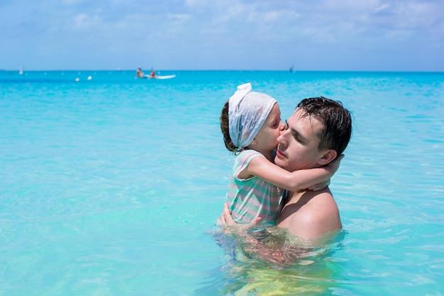 Pai feliz jogar com a filha no mar perfeito