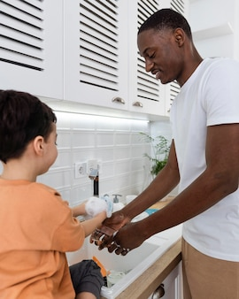 Pai feliz lavando pratos ao lado do filho