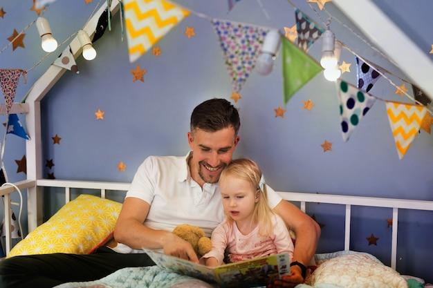 Pai feliz lendo livro com sua filha enquanto está sentado na cama antes de dormir juntos