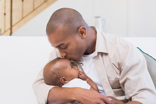 Pai feliz passando o tempo com o bebê no sofá