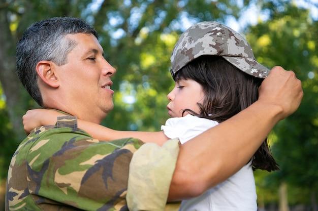 Pai feliz segurando a filha nos braços, vestindo a garota com seu boné de camuflagem. vista lateral. conceito de reunião familiar ou retorno a casa