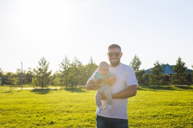 Pai feliz segurando filho bebê no conceito de natureza de família feliz dia dos pais e filho