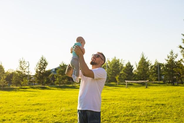 Pai feliz segurando o filho bebê jogando o bebê no ar conceito de família feliz dia dos pais e filho