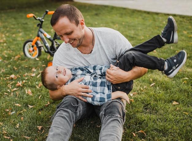 Pai feliz segurando o filho nos braços e brincando