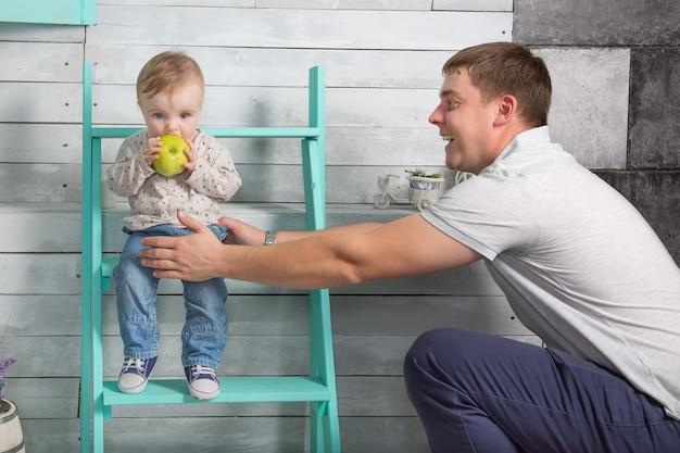Pai feliz segurando um menino que come uma grande maçã verde pai com filho sentado nos degraus internos