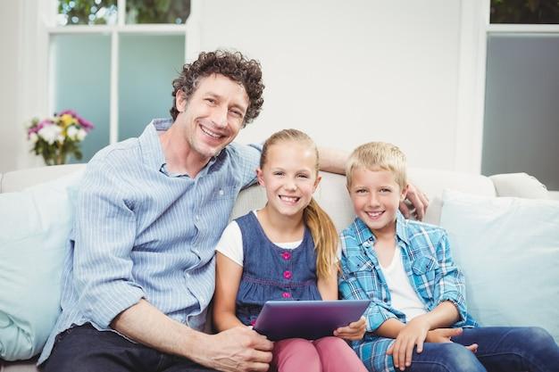 Pai feliz sentado com as crianças no sofá