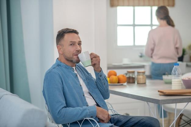 Pai feliz sentado na cozinha à mesa e bebendo chá e a filha em pé na janela