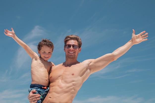 Pai feliz tem seu filho nos braços na praia com o oceano e o lindo céu azul ao fundo.