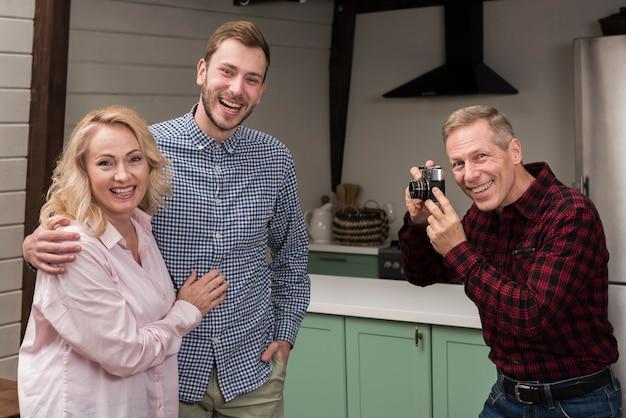 Pai feliz tirando foto de mãe e filho na cozinha