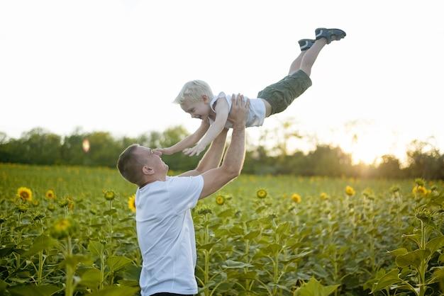 Pai feliz vomita seu filho pequeno no campo de girassóis