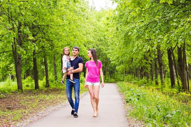 Pai, filha e mãe caminhando ao ar livre. família feliz.
